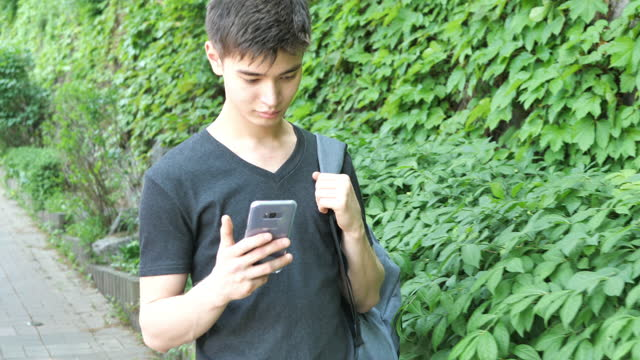 millennial guy with smart phone and backpack, going to school - 20 24 years stock videos & royalty-free footage