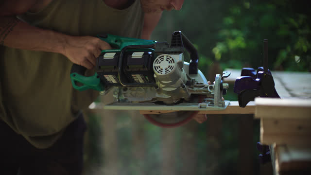 millennial hippie man cuts a plank of wood with a circular saw at his outdoor workshop - timber stock videos & royalty-free footage