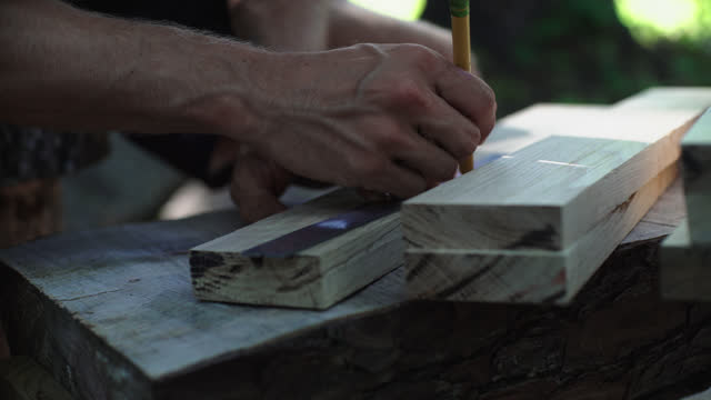 millennial hippie man sitting on a homemade log stool uses a pencil to measure a piece of wood at his outdoor woodworking shop - wood grain stock videos & royalty-free footage