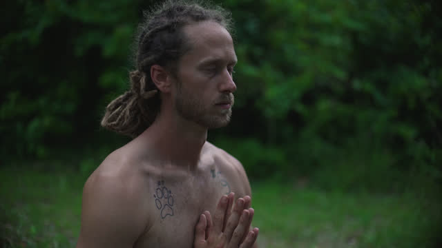 millennial hippie man with blonde dreadlocks moves into a prayer pose sitting on a yoga mat surrounded by nature - schneidersitz stock-videos und b-roll-filmmaterial