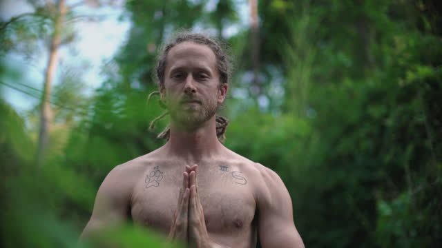 millennial hippie man with blonde dreadlocks moves into a prayer pose standing on a yoga mat surrounded by nature - schneidersitz stock-videos und b-roll-filmmaterial