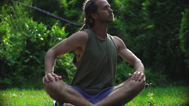 millennial hippie man with blonde dreadlocks stretches and sits in a prayer pose on a yoga mat surrounded by nature - schneidersitz stock-videos und b-roll-filmmaterial
