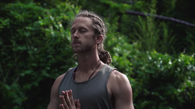 millennial hippie man with blonde dreadlocks stretches toward the sky and moves into a prayer position standing on a yoga mat in the grass surrounded by nature - dreadlocks stock videos & royalty-free footage