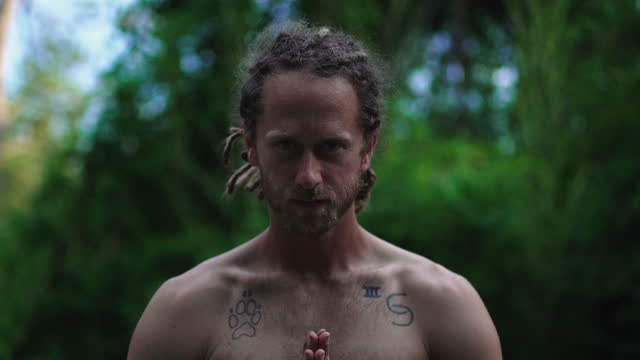stockvideo's en b-roll-footage met slo mo. millennial hippie man with blonde dreadlocks surrounded by nature stands in a prayer pose looking down and then looks up into the camera and smiles - dreadlocks