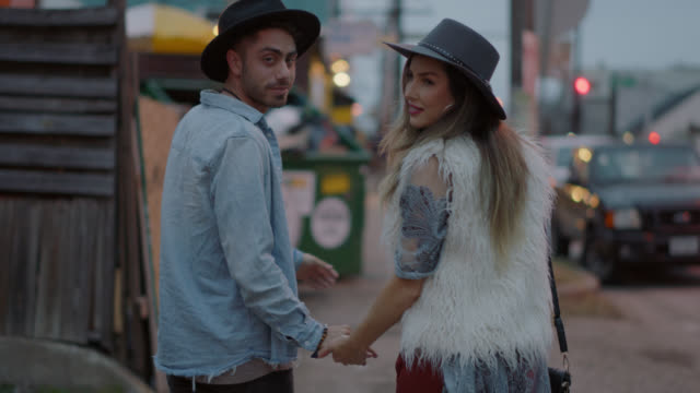slo mo. a millennial hipster couple hold hands while walking down a busy city street and turn around to look at the camera - holding hands stock videos & royalty-free footage