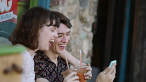 cu. a millennial hipster couple laughs on a bench outside a cafe while sipping smoothies and using an iphone - generation z点の映像素材/bロール