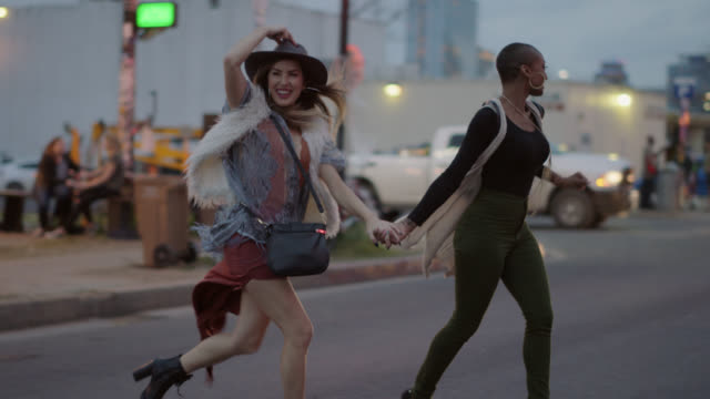 slo mo. a millennial hipster couple run across a busy city street outside a food truck - individualität stock-videos und b-roll-filmmaterial