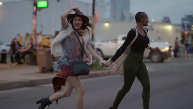 slo mo. a millennial hipster couple run across a busy city street outside a food truck - cool und lässig stock-videos und b-roll-filmmaterial