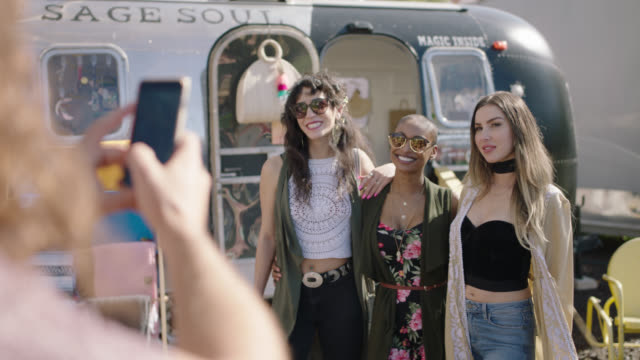 a millennial hipster man take a photo of diverse happy bohemian women trying on boho clothing from a mobile fashion truck - boho stock videos & royalty-free footage