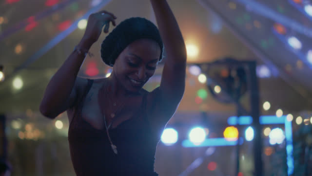 vídeos de stock e filmes b-roll de slo mo. a millennial hipster woman dances alone under the tent of a popular music festival - cultura jovem
