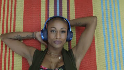 a millennial hipster woman is lying on a boho blanket listening to music on blue headphones - hörlurar bildbanksvideor och videomaterial från bakom kulisserna