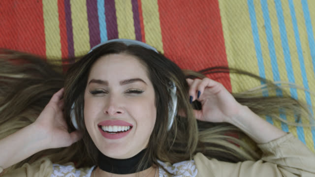 slo mo. cu. a millennial hipster woman is lying on a boho blanket listening to music on blue headphones - boho stock videos & royalty-free footage
