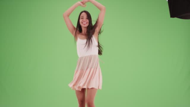 Millennial Latina dancing around in a dress on green screen