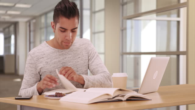 Millennial Latino university student in dorm working on laptop