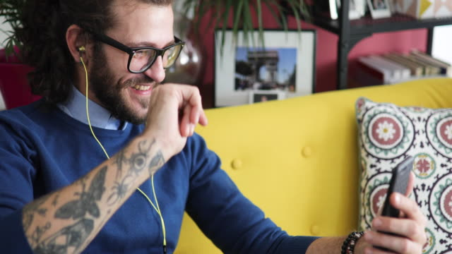 millennial mann video chattet mit freund - voip stock-videos und b-roll-filmmaterial