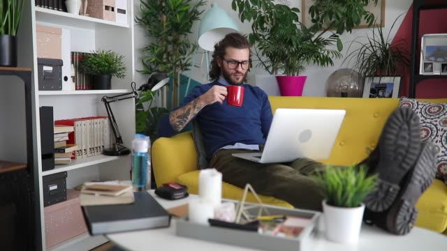 millennial man video chatting with friend - chignon video stock e b–roll