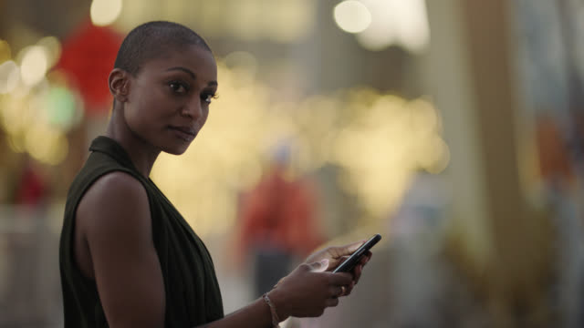 vidéos et rushes de a millennial mixed race hipster woman leans against a railing and types a text message on her iphone - blog