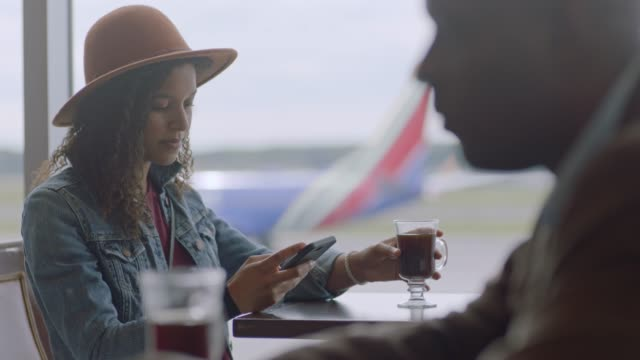 stockvideo's en b-roll-footage met millennial mixed-race female traveler sips coffee while looking at smartphone at airport terminal cafe. - travel destinations