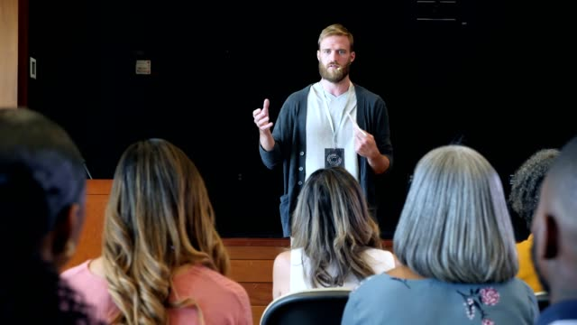 millennial motivational speaker talks to large crowd during conference - microphone stock videos & royalty-free footage