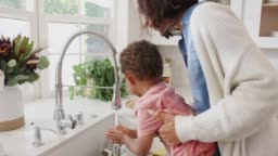 Millennial mum standing at the kitchen sink helping her son wash his hands, side view, close up