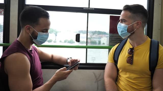 vídeos y material grabado en eventos de stock de turistas lgbt millennials con mascarillas en trasnportación pública - budapest