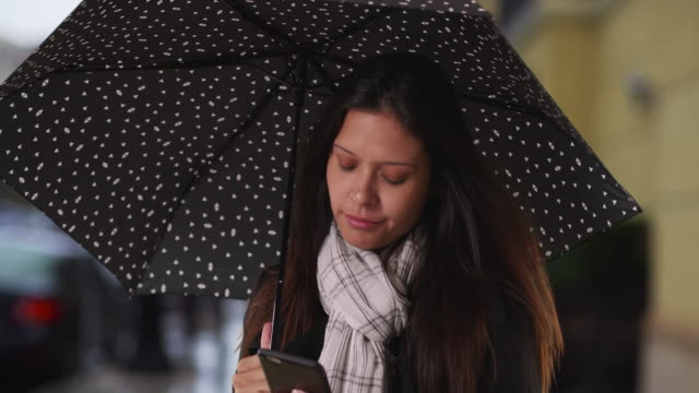 millennial woman in rainstorm on the street texting with mobile phone - polka dot stock videos and b-roll footage