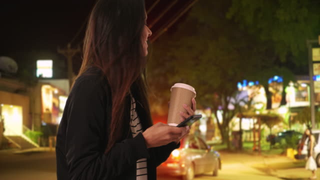 Millennial woman laughs at text from friend while on Costa Rican street at night