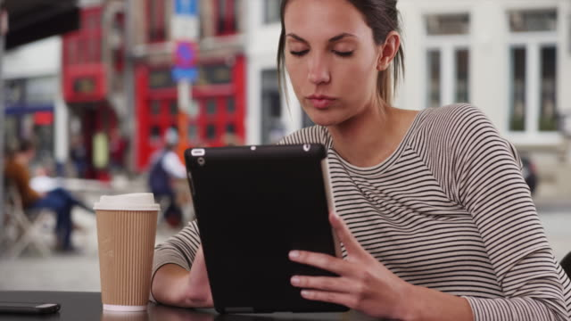 millennial woman sitting at cafe table with tablet sitting outside city cafe - bericht stock-videos und b-roll-filmmaterial