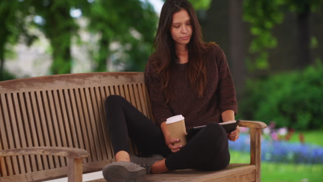 millennial woman sitting on park bench reading on tablet and drinking coffee - coffee drink stock videos & royalty-free footage
