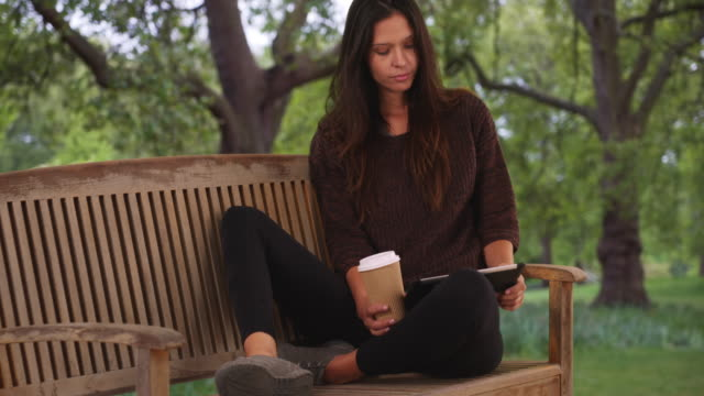 millennial woman sitting on park bench using tablet computer and drinking coffee - coffee drink stock videos & royalty-free footage