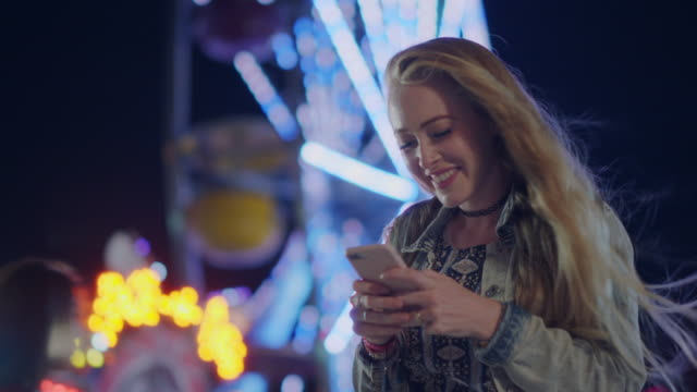 a millennial woman takes a selfie in front of a ferris wheel of a carnival - adolescence stock videos & royalty-free footage
