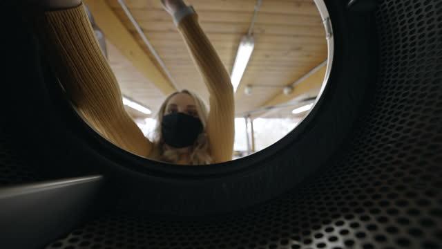 コインランドリーで洗濯をしている保護フェイスマスクを持つミレニアル世代の女性 - コインランドリー点の映像素材/bロール