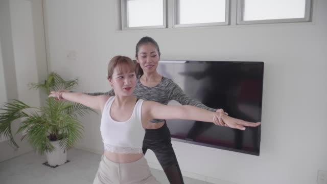 ミレニアル世代の女性がコーチからヨガを学び、練習する - yoga点の映像素材/bロール