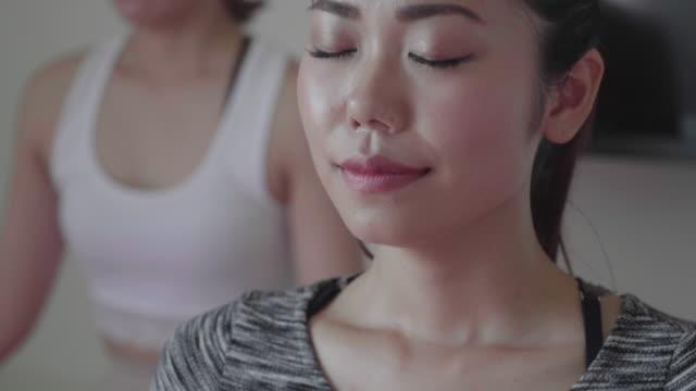 ヨガのクラスで呼吸の抜粋で瞑想するミレニアル世代の女性 - yoga点の映像素材/bロール