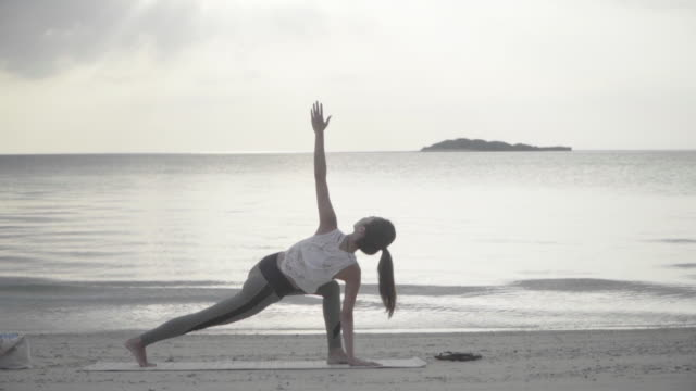 millennial-aged women practicing yoga on a beach in a remote location - mindfulness stock videos & royalty-free footage