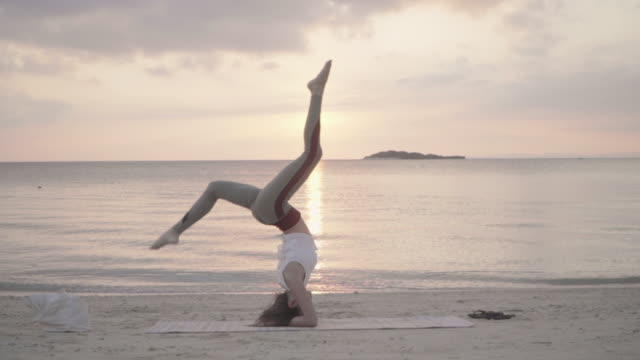 millennial-aged women practicing yoga on a beach in a remote location - stretching stock videos & royalty-free footage