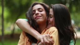 Millennials LGBT girlfriends kissing and hugging outdoors