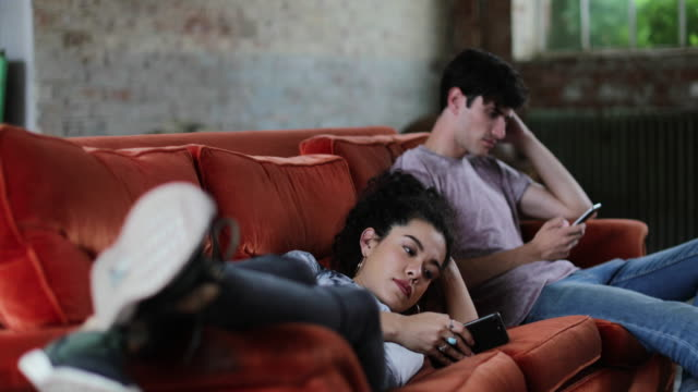 millennials using smartphones relaxing on sofa - faulheit stock-videos und b-roll-filmmaterial