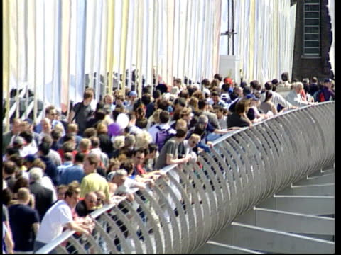 vídeos de stock e filmes b-roll de repair costs lib england london people crossing the millennium bridge millennium bridge swaying pull out - oscilar