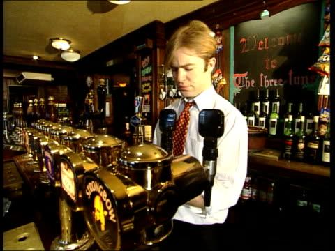 vídeos y material grabado en eventos de stock de celebration plans altn chris england london int barworker putting out ashtrays on bar in pub barman at pumps cs nozzles of beer pumps being removed... - el milenio