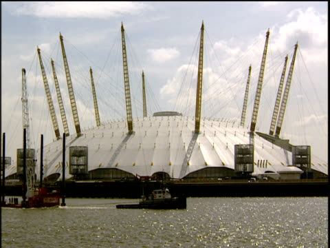 Millennium Dome from Thames River a tug boat with tow floats through from left to right London