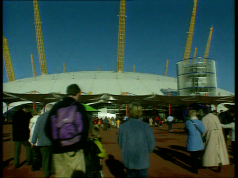 profits row; lib ext day people arriving at the dome lib int large inflatable figure greeting visitors banknotes on display inside money zone track - millennium dome video stock e b–roll