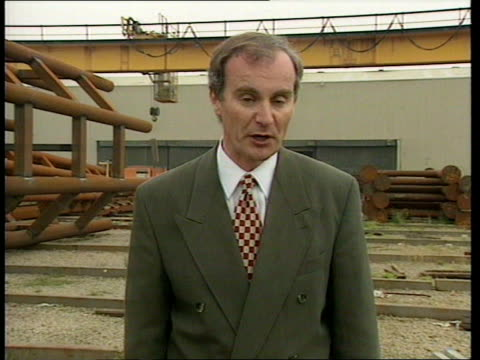 Short attack ITN ENGLAND Lancs Bolton i/c Minister in charge of package Peter Mandelson MP along at factory wearing hard hat Workers in factory...