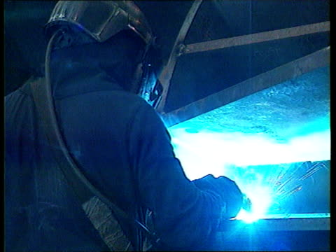 Short attack ITN Lancs Bolton Minister in charge of package Peter Mandelson MP along at factory wearing hard hat Workers in factory welding masts for...