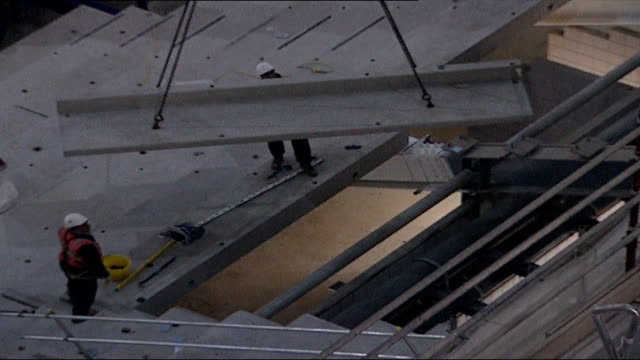 millennium dome to re-open as o2 centre; new stairway under construction top shot workers moving girder into place close shot face of welder at work... - 桁橋点の映像素材/bロール