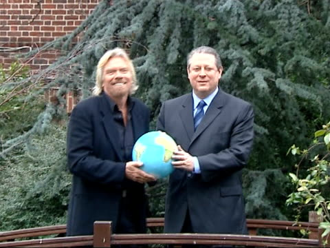 25 million dollar prize offered for global warming solution england ext richard branson and al gore stand togehter holding globe at photocall - 環境メディア賞点の映像素材/bロール