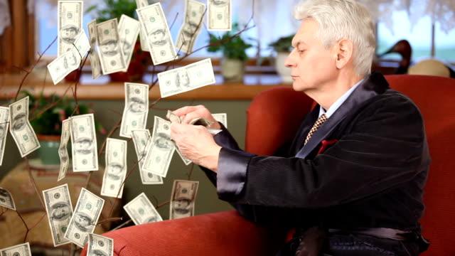 millionaire in armchair picking 100 dollar bills off money tree - millionnaire stock videos & royalty-free footage