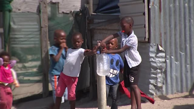 millions face water shortages in cape town; t010218014 / tx south africa: cape town: siqalo township: ext children collecting water at standpipe man... - cape town stock videos & royalty-free footage