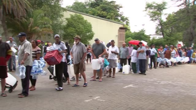 Millions face water shortages in Cape Town T010218033 / TX Cape Town EXT People queuing for water by 'Stop' sign PAN People with containers in water...