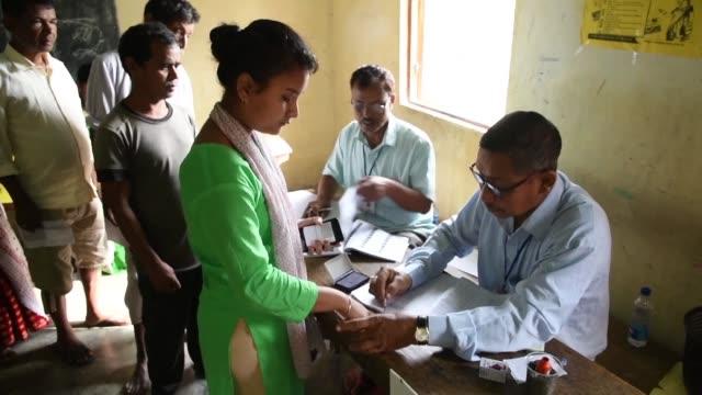 millions of voters begin to cast ballots including women from the bodo tribe in northeastern assam state as the second phase of india's enormous... - röstsedel bildbanksvideor och videomaterial från bakom kulisserna